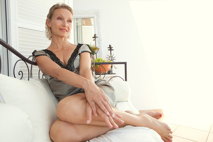 mature senior woman lounging on a day bed