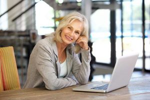 Portrait of beautiful older woman working laptop computer